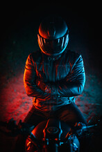 Biker With Black Helmet And Crossed Arms At Night And Colorful Lights