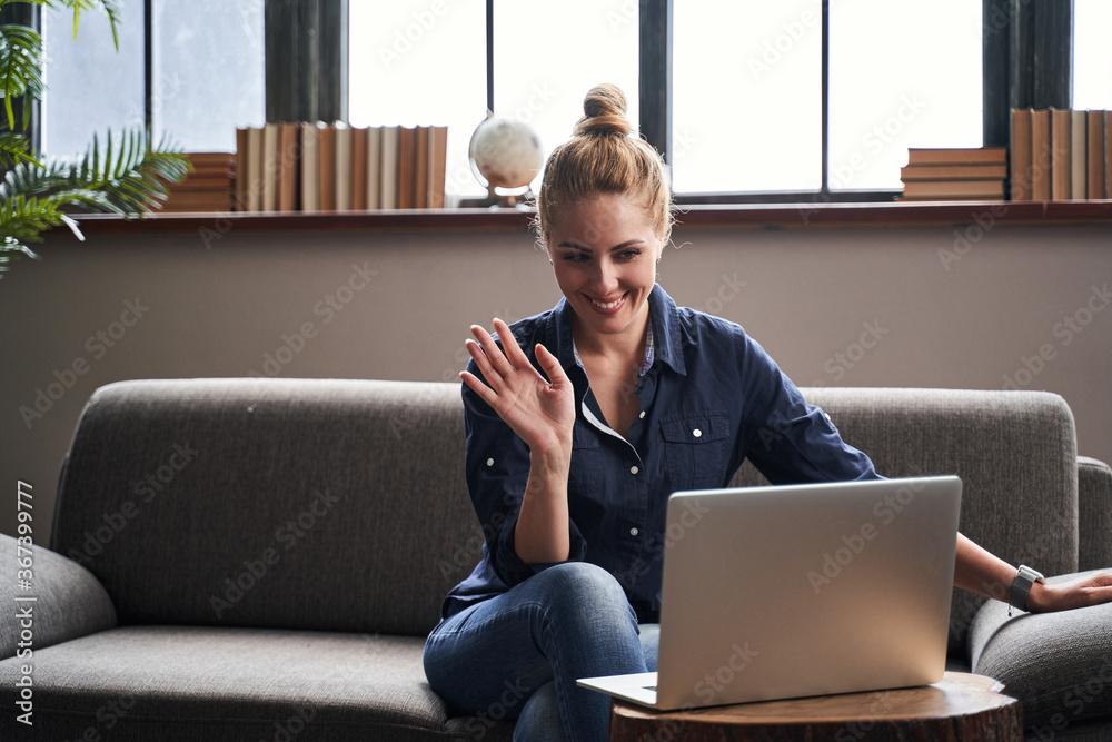 Fototapeta Friendly woman waving her hand in online meeting