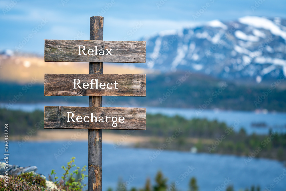 Fototapeta relax reflect recharge text on wooden signpost outdoors in landscape scenery during blue hour. Sunset light, lake and snow capped mountains in the back.