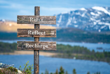 Relax Reflect Recharge Text On Wooden Signpost Outdoors In Landscape Scenery During Blue Hour. Sunset Light, Lake And Snow Capped Mountains In The Back.