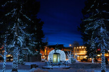Lights On Elk Antler Arches And Trees In Jackson Wyoming Town Square In Winter At Twilight With Cowboy On Bucking Broncho Statue
