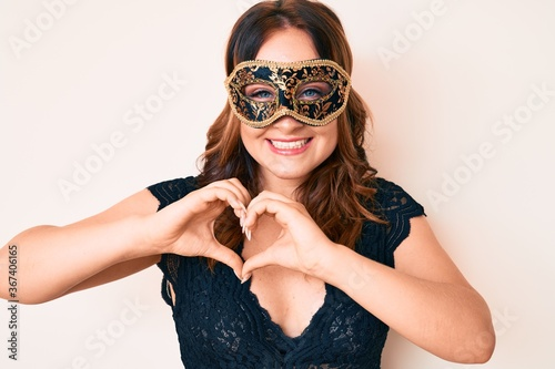 Fototapeta Young beautiful caucasian woman wearing venetian carnival mask smiling in love doing heart symbol shape with hands