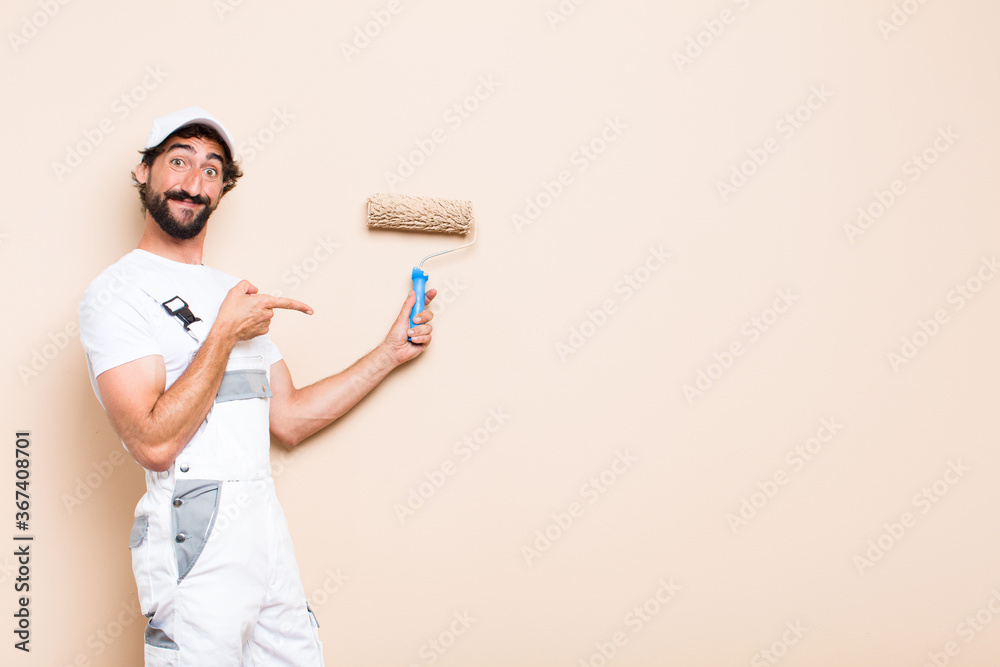 Fotografía young painter bearded man pointing expression and holding a roll