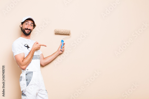 Cuadros en Lienzo young painter bearded man pointing expression and holding a roll