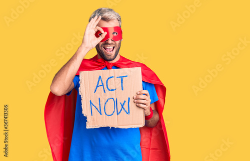 Photo Young blond man wearing super hero costume holding act now cardboard banner smil