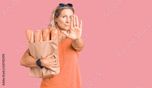 Photo Middle age fit blonde woman holding paper bag with bread with open hand doing st