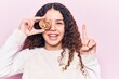 Beautiful kid girl with curly hair holding cookie smiling with an idea or question pointing finger with happy face, number one