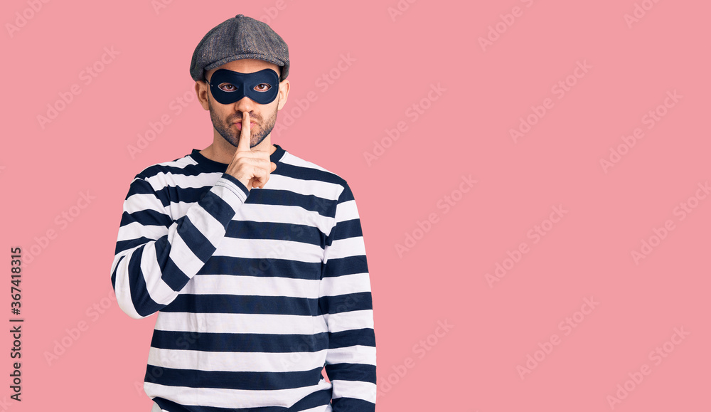 Fototapeta Young handsome man wearing burglar mask asking to be quiet with finger on lips. silence and secret concept.