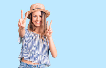 Obraz na płótnie Canvas Young beautiful girl wearing hat and t shirt smiling looking to the camera showing fingers doing victory sign. number two.