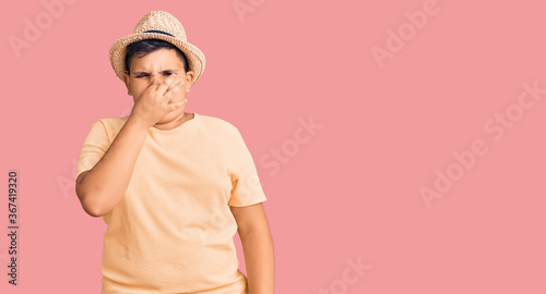 Little boy kid wearing summer hat and hawaiian swimsuit smelling something stinky and disgusting, intolerable smell, holding breath with fingers on nose Fotobehang