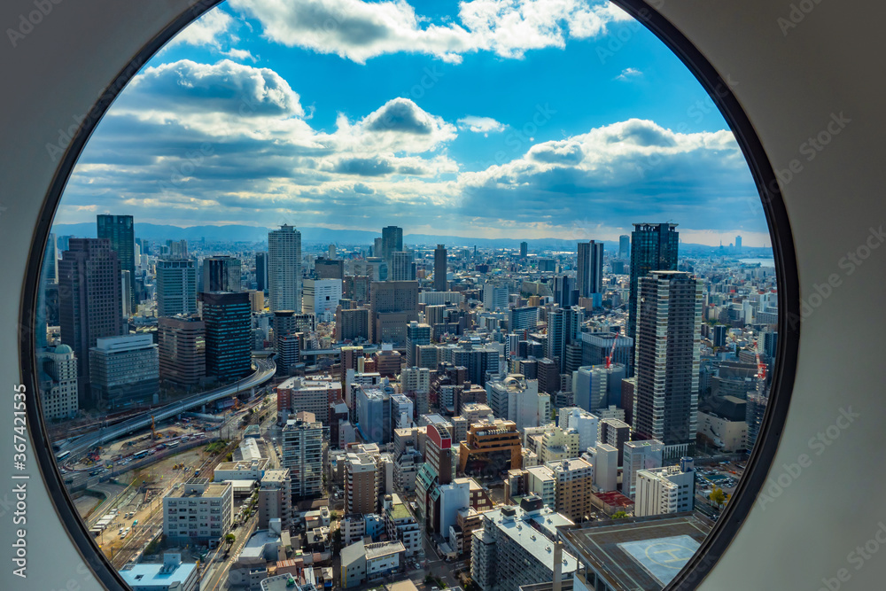 Fototapeta Japan. Osaka. View of Osaka from the window. Panorama of Osaka from a height. Island of Honshu. The urban landscape of Japan. Urbanistics. Modern buildings in Japan. House with helipad.