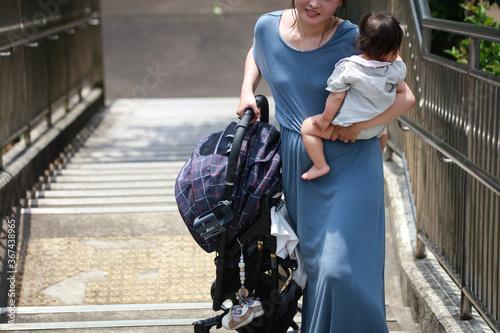 ベビーカーを持ち上げ階段を上る母親 Canvas