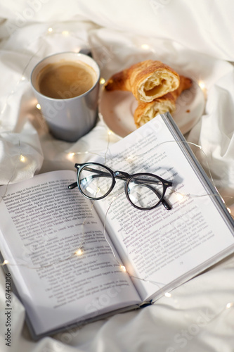 morning, hygge and breakfast concept - croissants, cup of coffee, book and glasses in bed at home