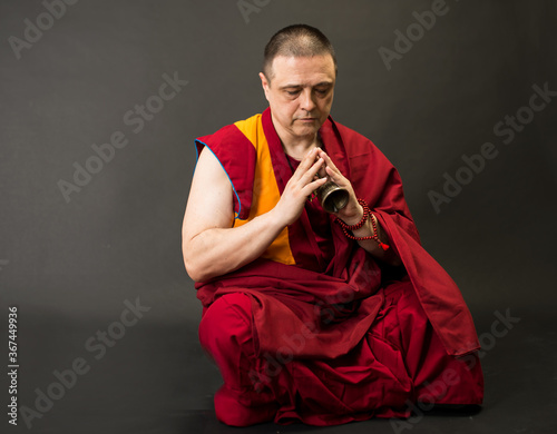 Tela Tibetan Buddhist monk teacher in a burgundy yellow outfit suit