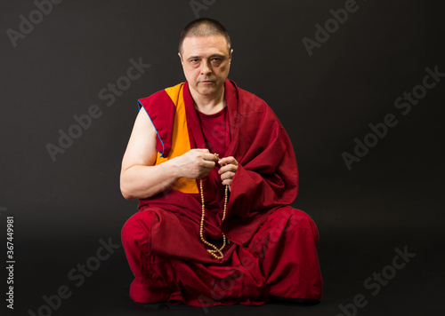 Photo Tibetan Buddhist monk teacher in a burgundy yellow outfit suit