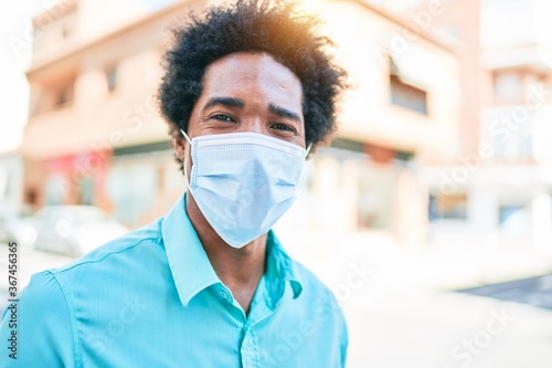 Young handsome african american man wearing casual clothes and medical mask smiling happy walking at town street. - 367456365