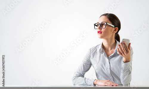 Smiling young woman sits at desk Canvas-taulu