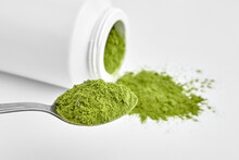 Green Freeze Dried Wheatgrass Powder In Steel Tea Spoon And White Plastic Container.