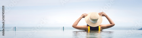 Rear view of asian woman relax at pool resort with outdoor panorama sea view Fotobehang