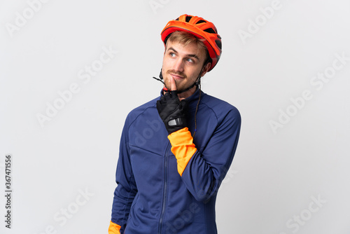 Tablou Canvas Young cyclist blonde man isolated on white background thinking an idea while loo