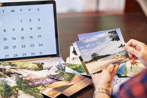 Fototapeta Hands of traveler checking photos he printed after summer vacation obraz