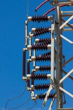 Close Up Taken Of High Voltage Line Metal Pole Aganist Blue Sky.