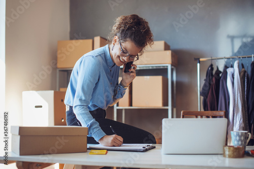 Fototapeta Small business owner. Women, owner of small business packing product in boxes preparing it for delivery. obraz