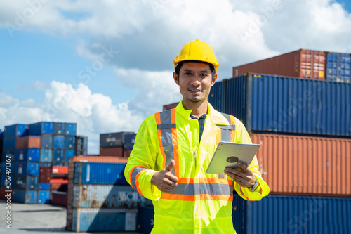 Fototapeta Young worker man with digital tablet at container terminal port,Business Logistics import export shipping concept