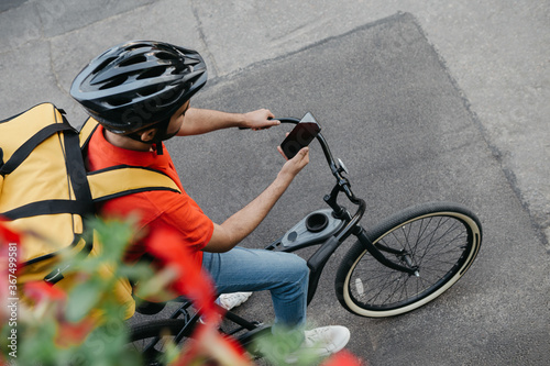 Fototapeta Bicycle courier in protective helmet with delivery backpack sits on bicycle and looks at phone and uses online map on street obraz