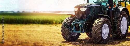 Fototapeta agricultural machinery farm equipment - tractor standing on the field. banner copy space obraz