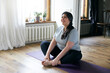 Cheerful attractive young overweight woman in activewear choosing healthy lifestyle, sitting on mat with hands on bare feet, doing butterfly yoga exercise, stretching thighs. Body shape and activity
