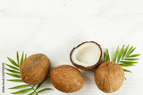 Top view shot of coconuts, whole and cracked on halves on paper textured background with a lot of copy space for text. Background with raw fruit of tropical palm. Flat lay.