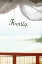 The Word Family Cut Out Of Wooden Letters And Painted White Hanging On The Terrace With White Tulle. The Ocean Is Out Of Focus In The Background