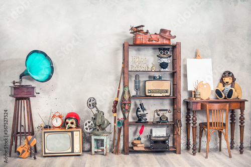 Collection of antique media devices, writers tools, gramophone, film projector, old Teddy Bear toy with canvas blank on easel, travel bag front concrete wall background. Vintage style filtered photo - 367527524