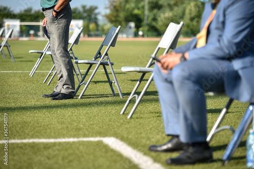 Photographie Chairs on the turf of a soccer field maintaining the social distance imposed by