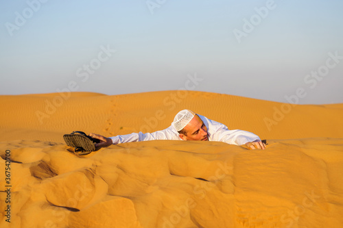 Photo Portrait of thirsty Arabic man on a middle of yellow desert.