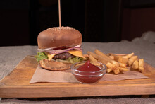 Delicious And Hearty Cheeseburger With Fries And Ketchup On A Wooden Tray