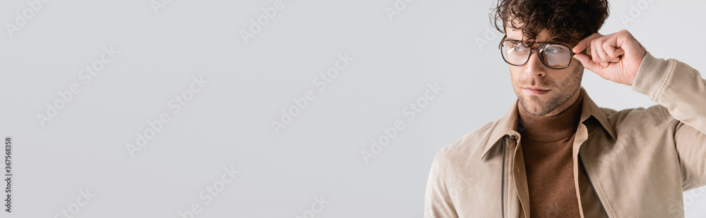 Fototapeta horizontal image of stylish, handsome man touching glasses and looking away isolated on grey