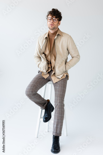 full length view of trendy man sitting on stool, holding hands in pockets and looking at camera on grey