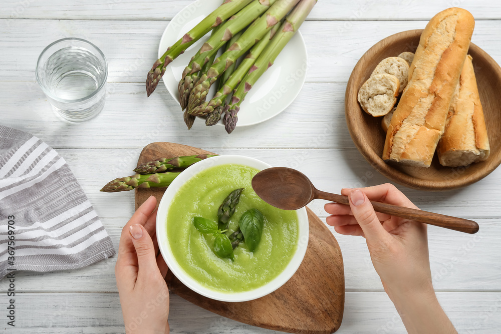 Fototapeta Woman eating delicious asparagus soup at white wooden table, top view