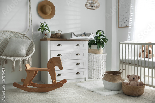 Obraz Chest of drawers with changing tray and pad near comfortable cradle in baby room. Interior design - fototapety do salonu