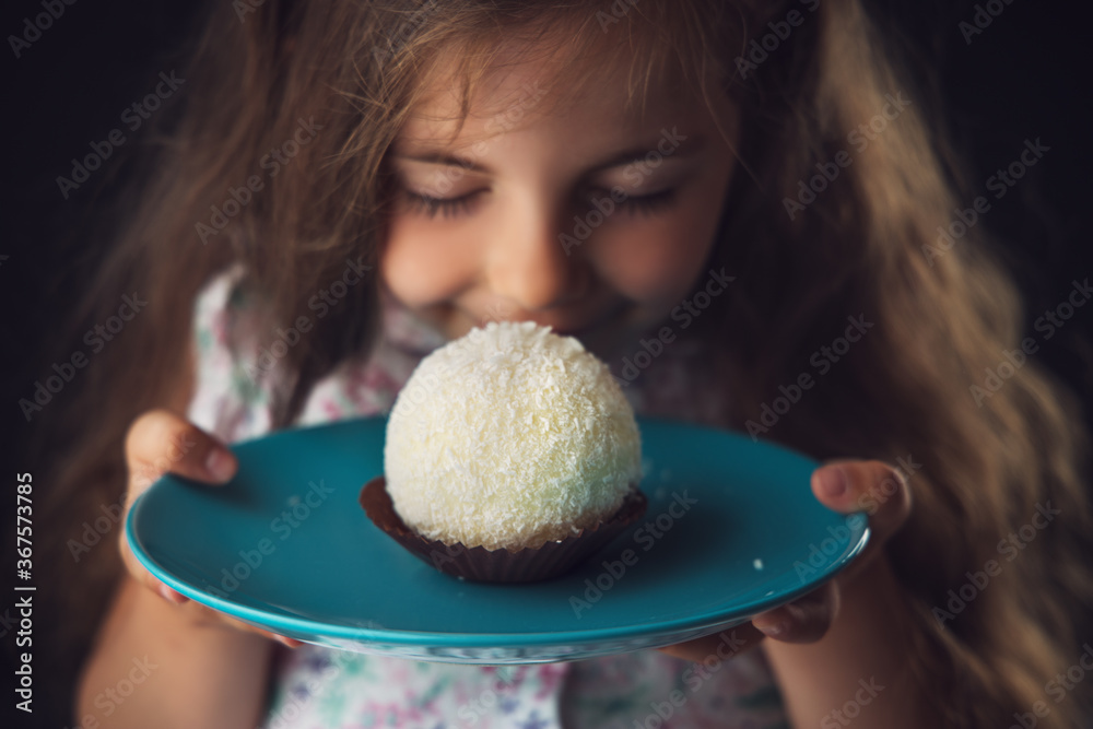 Fototapeta Beautiful little girl surprised from a tasty big chocolate coconut candy as a ball. Kid ready to eat cake.