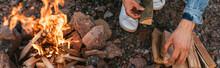 Panoramic Concept Of Man Touching Wooden Log Near Burning Bonfire