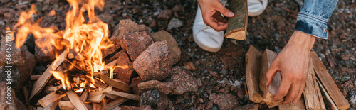 Fototapeta panoramic concept of man touching wooden log near burning bonfire