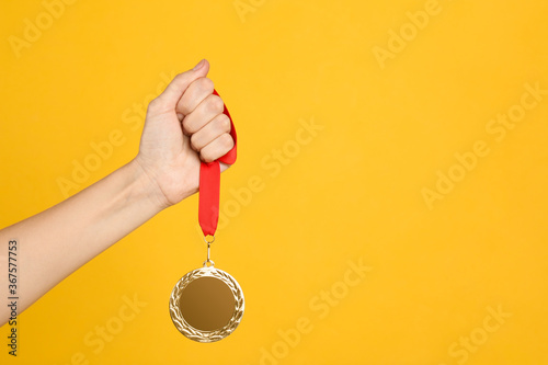 Woman holding golden medal on yellow background, closeup Wallpaper Mural