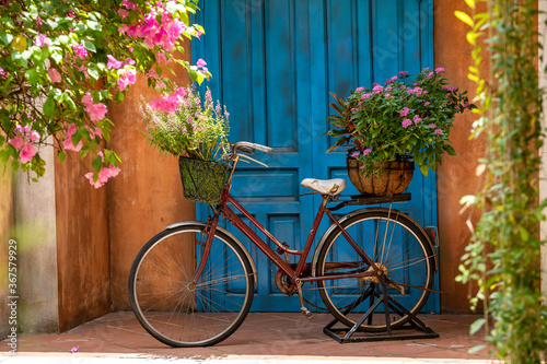Fotografiet Vintage bike with basket full of flowers next to an old building in Danang, Viet