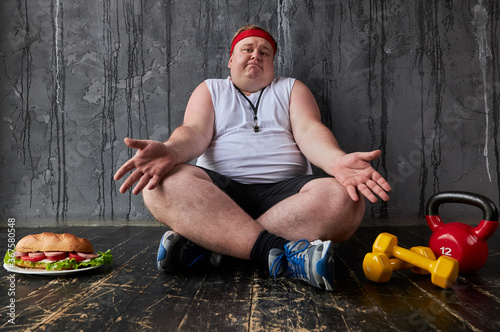 obese fat caucasian man can not decide whether to train or eat, male sits on the floor and choose eat unhealthy food or doing sport exercises