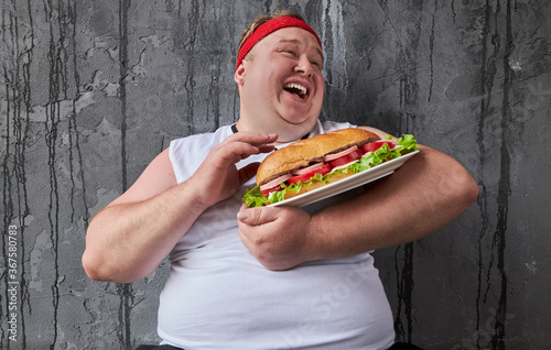 happy caucasian overweight guy stroking a sandwich, he treats food with care isolated over gray background