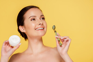 Obraz na płótnie Canvas smiling naked beautiful woman holding cosmetic cream and jade roller isolated on yellow
