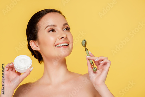 smiling naked beautiful woman holding cosmetic cream and jade roller isolated on yellow